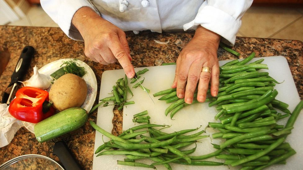 A chef preps a side dish in a client's kitchen. (Credit: Alamy)