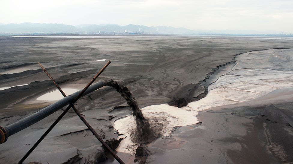 Black sludge pours into the lake - one of many pipes lining the shore (Credit: Liam Young/Unknown Fields)