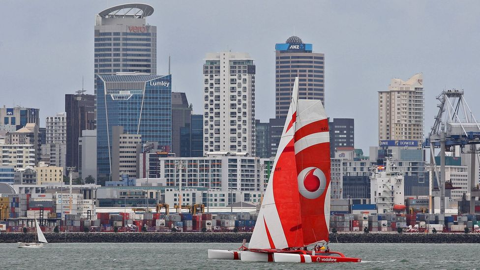 A yacht sets sail past the central business district during a regatta at Waitemata Harbour. (Credit: Sandra Mu/Getty Images)