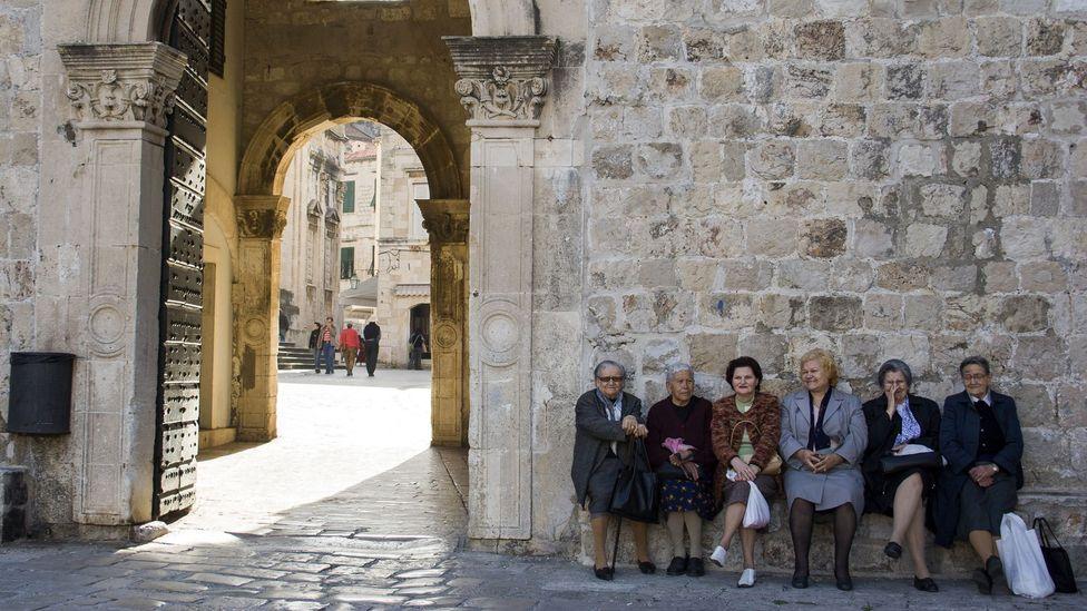 Women sitting by Dubrovnik's city walls (Credit: Santiago Urquijo/Getty)