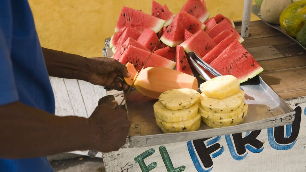 A man slices a papaya at a fruit stand in Cartagena (Credit: Jupiterimages/Getty)