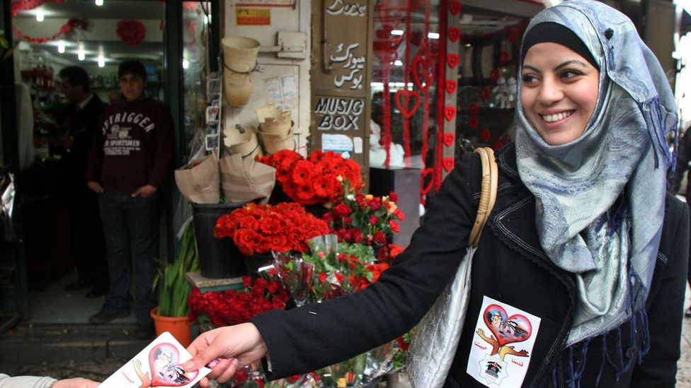 """A woman hands out stickers saying """"Jerusalem is my love"""" (Credit: AFP/Getty)"""