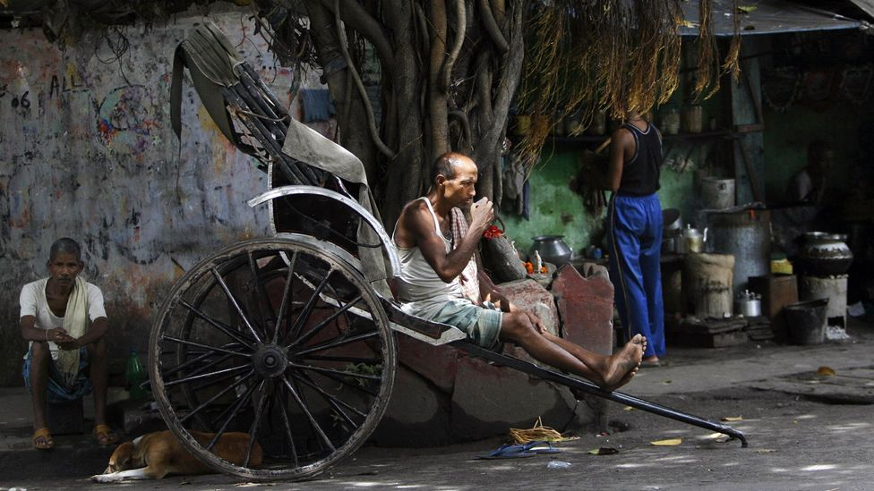 Rickshaw puller finds a moment of peace sipping tea (Credit: Deshakalyan Chowdhury/Getty)