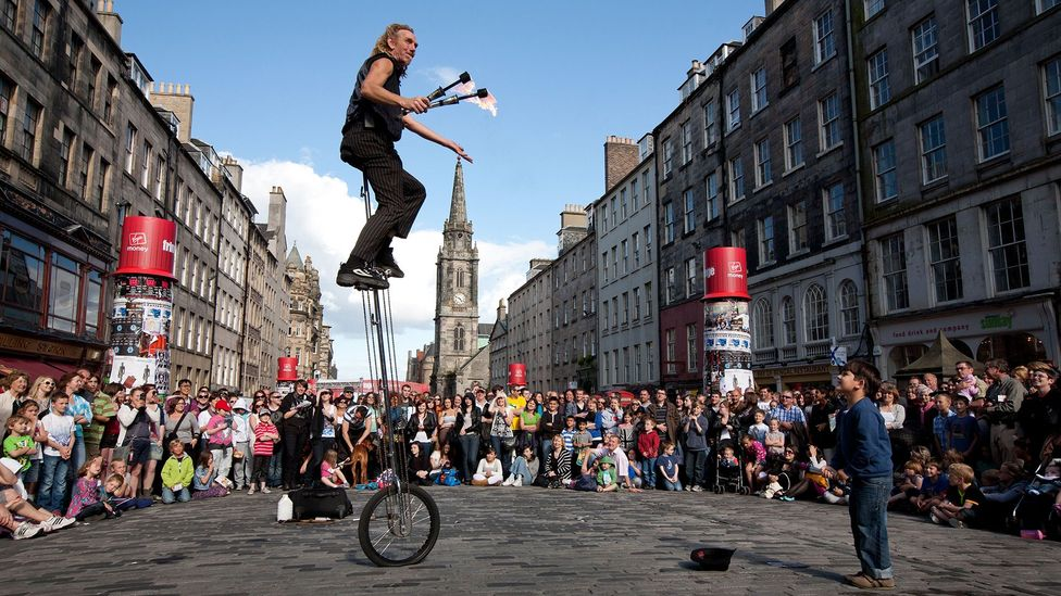 Crowds gather on the Royal Mile to watch performers during the Fringe Festival. (Credit: Jeremy Sutton-Hibbert/Alamy Stock Photo)