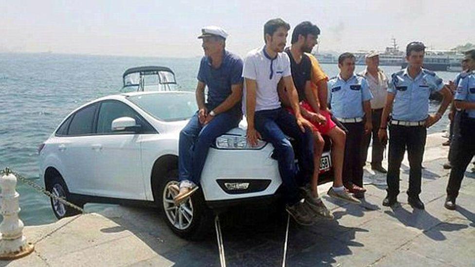 Several men nonchalantly perched on the bonnet.