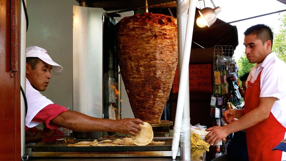 The pork is placed inside a corn tortilla after it's carved off (Credit: CarlosVanVegas/Mexico City – Streetfood/Flickr/CC BY 2.0)