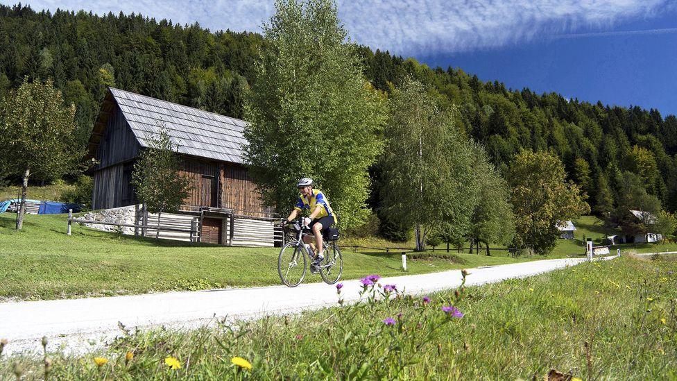 A single cyclist rides Bohinj's quiet country roads (Credit: Rebecca E Marvil/Getty)