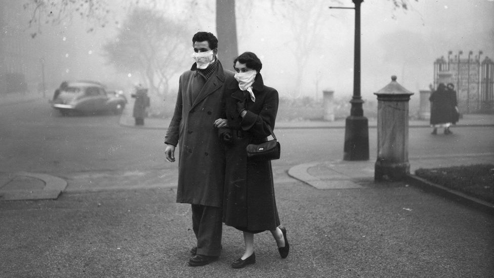 A couple walks the streets of London in November 1953; nearly a year after the Great Smog, masks were still necessary (Credit: Monty Fresco/Topical Press Agency/Getty Images)