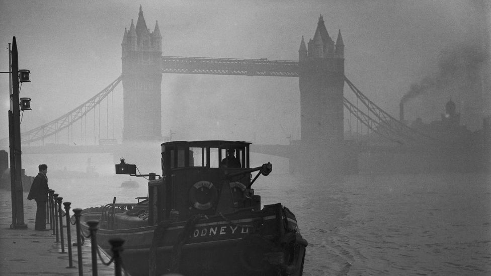 A man looks out at the Tower Bridge during the Great Smog of 1952 (Credit: Fox Photos/Hulton Archive/Getty Images)