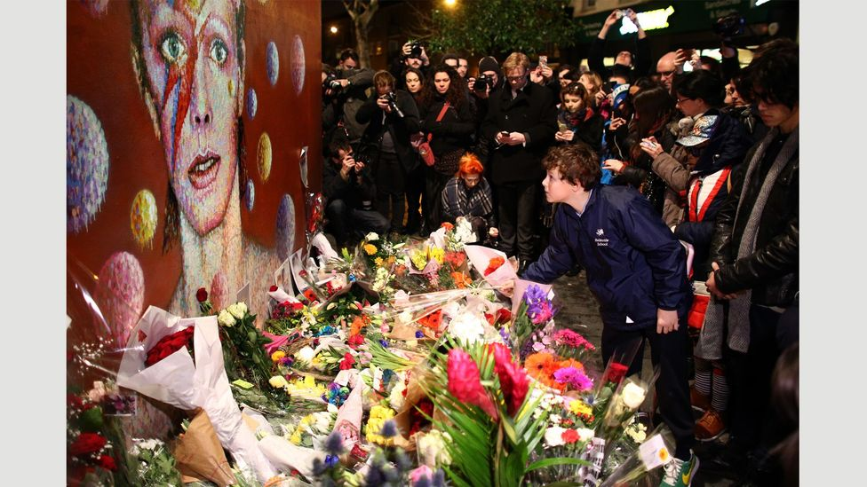 Mourners pay tribute to David Bowie at a mural of Aladdin Sane in Brixton (Credit: Carl Court/Getty Images)