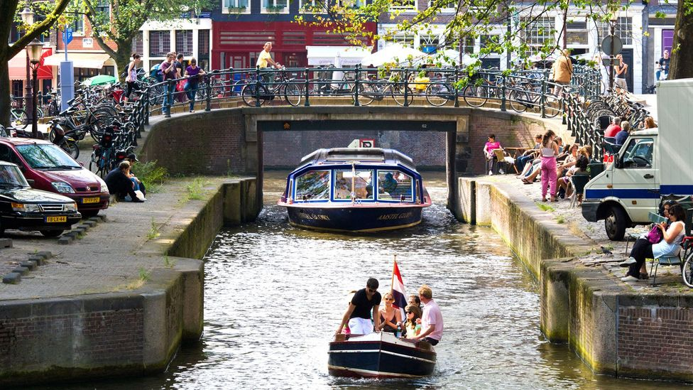 People enjoy life along Amsterdam's famous canals (Credit: Wim Wiskerke/Alamy)