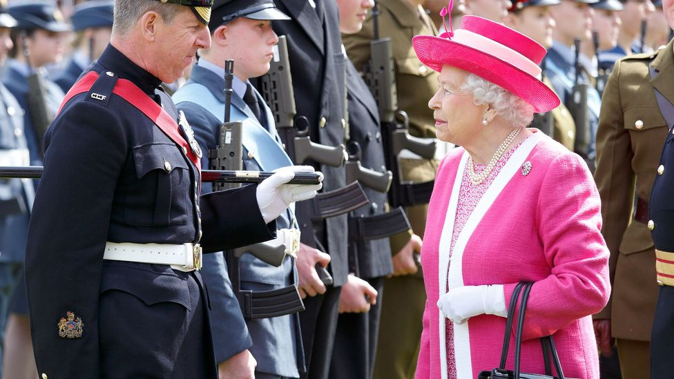 The head-to-toe, colour-blocked daywear and matching hats that the monarch favours for her public engagements have become her personal brand (Credit: Getty Images)