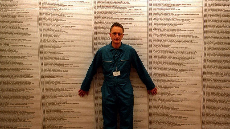 Landy stands in front of the exhaustive catalogue of his 7,227 of his belongings – in the end all that remained was his blue boiler suit (Credit: Michael Landy/Parisa Taghizadeh)