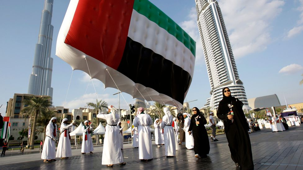 Emirati men and women carry a UAE flag in front of the Burj Khalifa during United Arab Emirates National Day, Dubai (Credit: Getty Images)