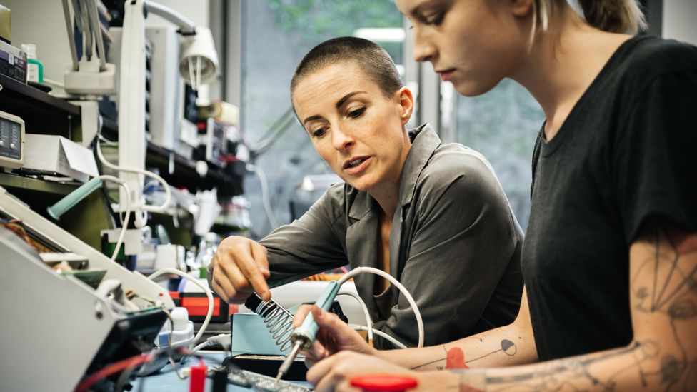 Female technician guiding a young trainee on repairing an electronical device (Credit: Getty Images)