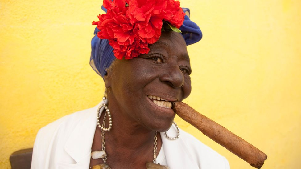 Older Cuban woman posing for tourist with cigar in mouth, Old Cathedral Square, Cuba (Credit: Getty Images)