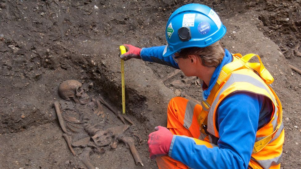 An archaeologist measures the depth of a human skeleton, one of 25 that were found during excavations for London's Crossrail line at Farringdon (Credit: Amer Ghazzal/Alamy)