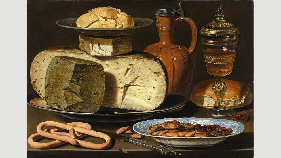 A distorted reflection of a figure thought to be Clara Peeters can be seen in the metal lid of the jug in her Still Life with cheeses, Almonds and Pretzels (Credit: Mauritshuis)