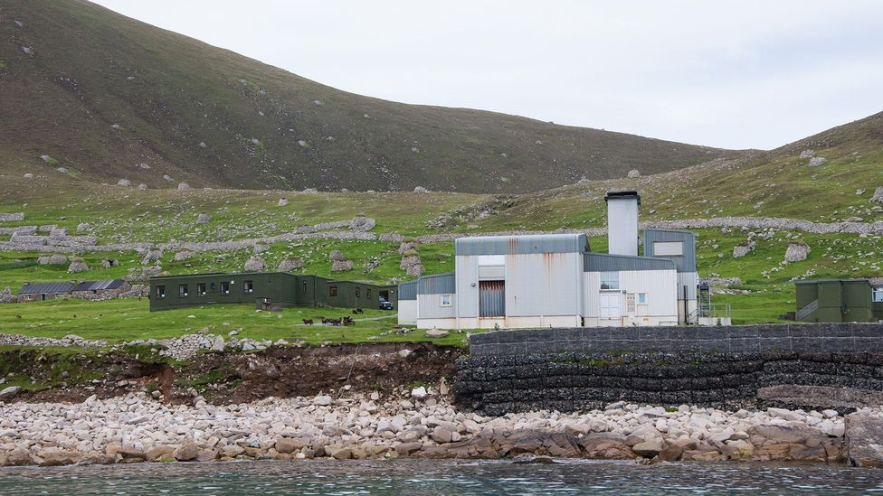 From the harbour at Hirta, the military installations run by the Ministry of Defence seem to dwarf the remnants of the abandoned village, behind (Credit: Amanda Ruggeri)