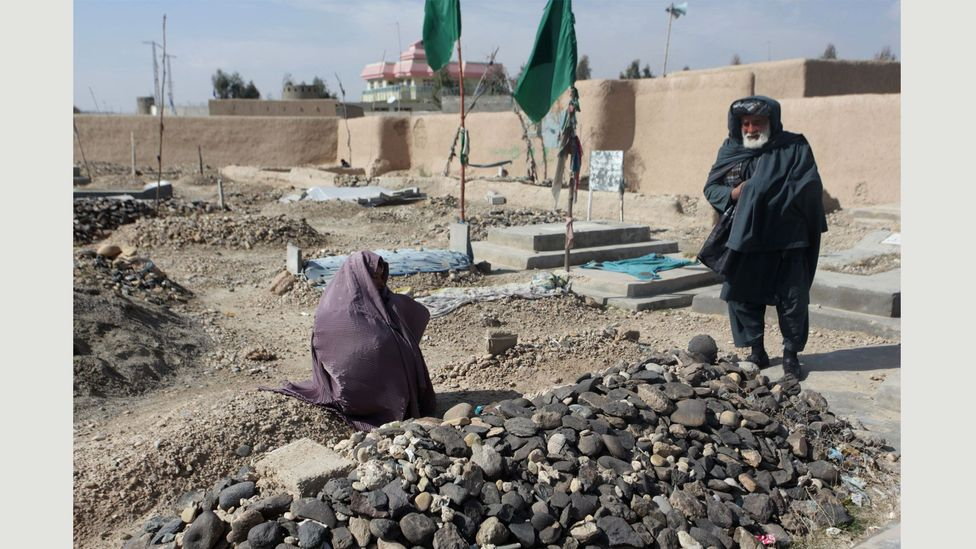 The parents of the late poet RahilaMuska are photographed next to her grave in Gereshk: they denied that their daughter wrote poetry (Credit: Seamus Murphy/Panos Pictures)