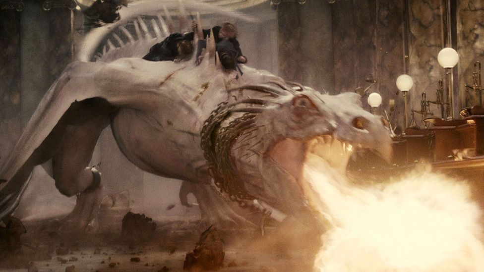 Harry, Hermione and Ron ride on the back of a dragon that guards a vault at Gringotts bank in Harry Potter and the Deathly Hallows – Part 2 (Credit: Warner Bros)