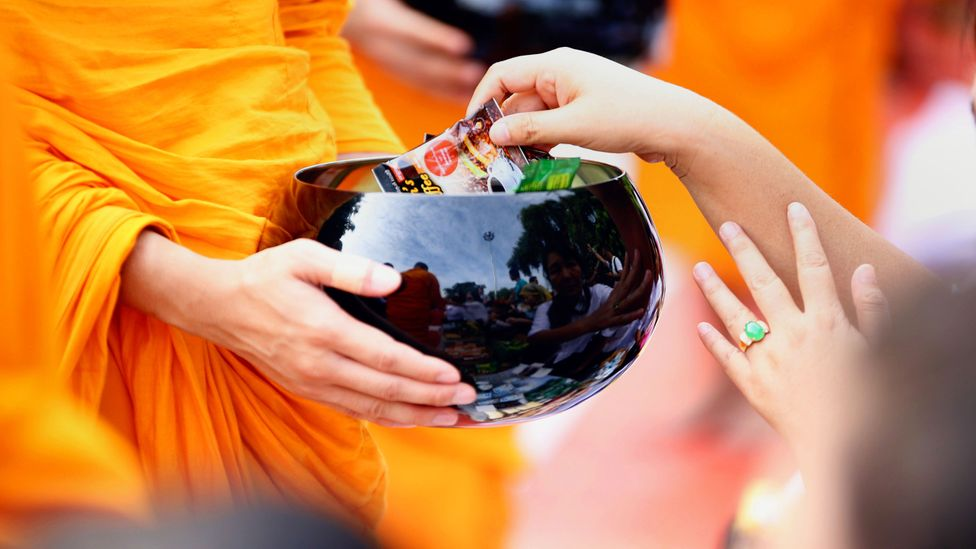 A Buddhist monk receives alms (Credit: PHYO MG MG/AFP/Getty Images)
