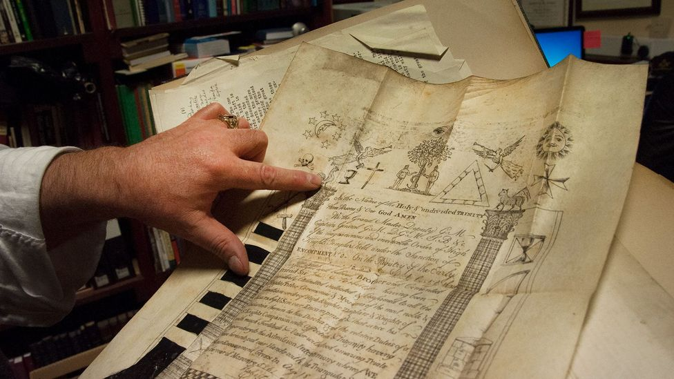 Cooper points to the Masonic symbols on one of the many historic documents in the lodge's archive (Credit: Amanda Ruggeri)