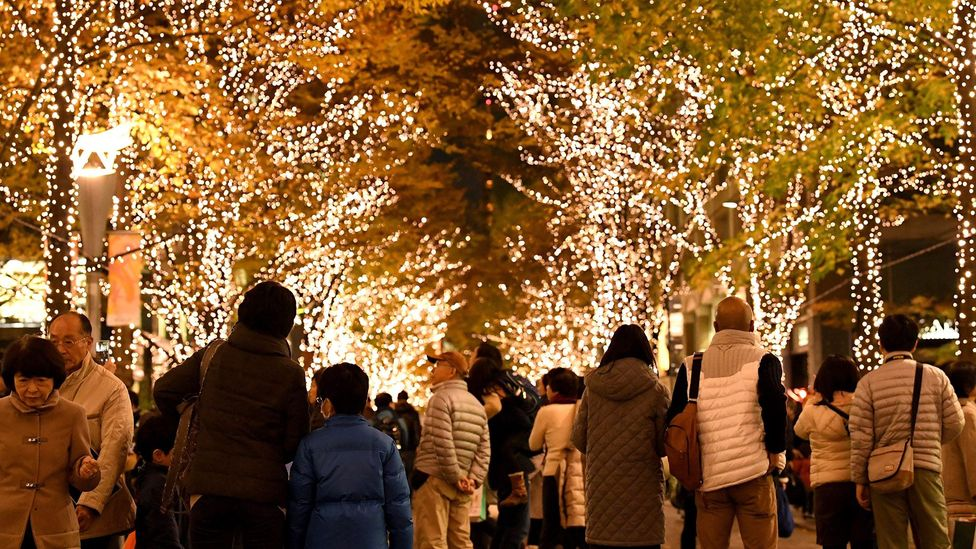 People walk beneath Christmas decorations in the Marunouchi shopping district of Tokyo on December 2, 2016 (Credit: Getty Images)