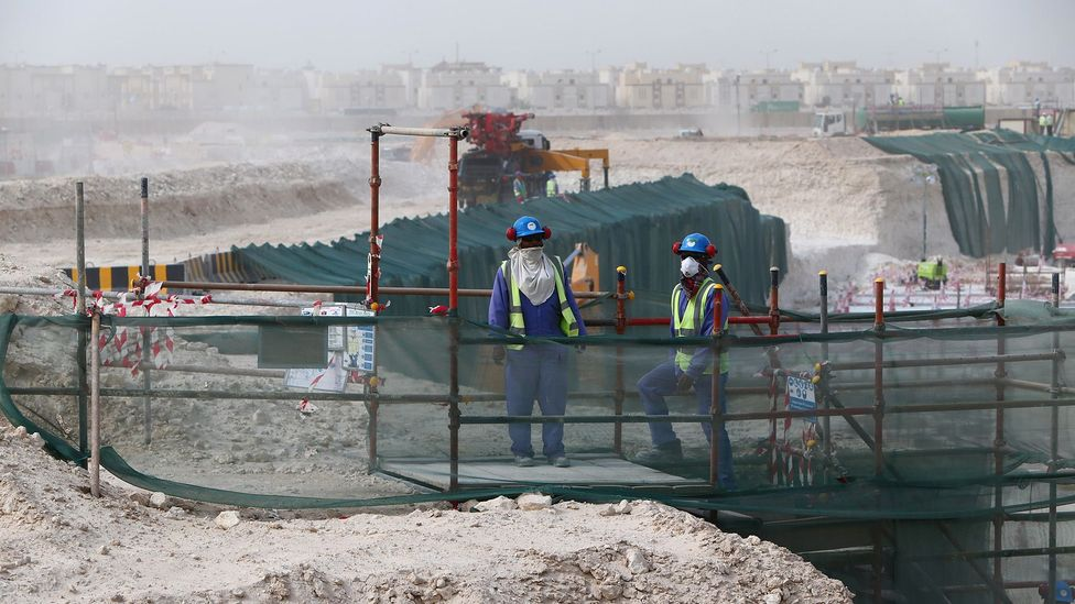 Foreign laborers work at the construction site of a football stadium in Qatar in 2015 (Credit: Getty Images)