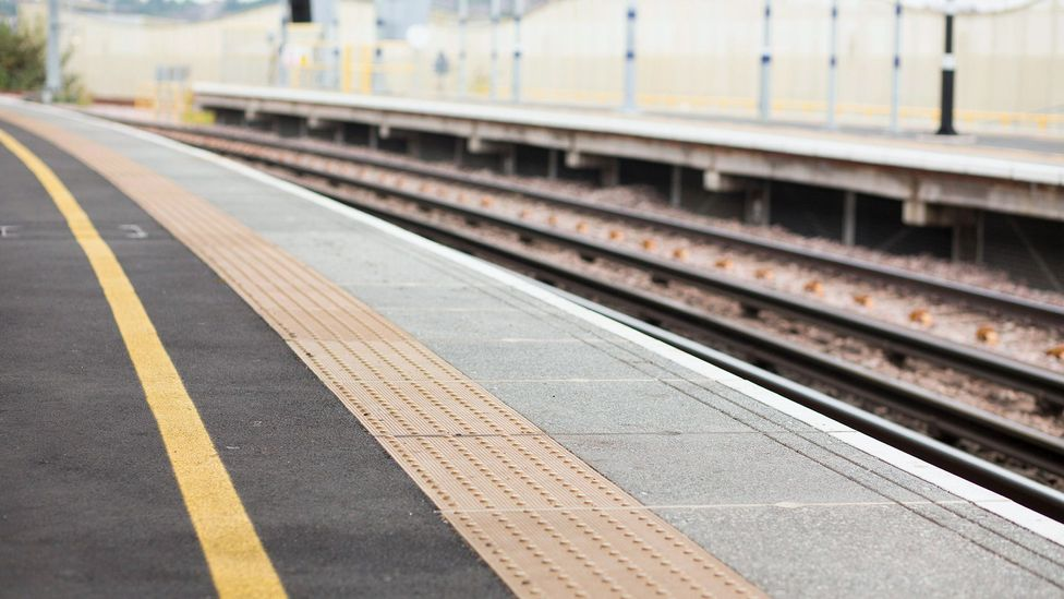 The edge of a train platform is marked by coloured slabs with flat-topped domes (Credit: Alamy)