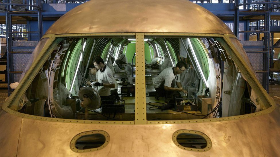 Brazilian technicians assemble an aircraft at the production line of Embraer (Credit: Getty Images)