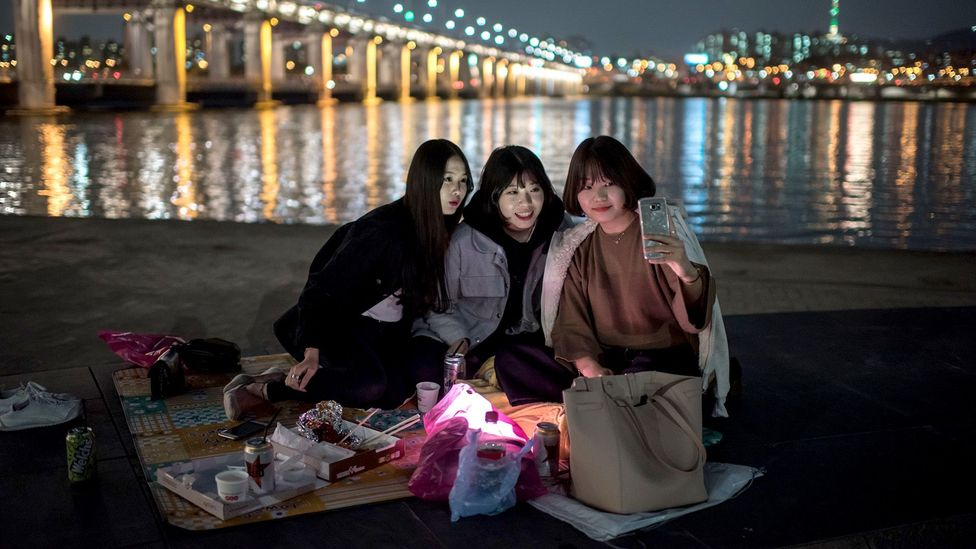 A group of women look at a smartphone near the Han River. South Korea has the highest percentage of smartphone users in the world (Credit: Getty Images)