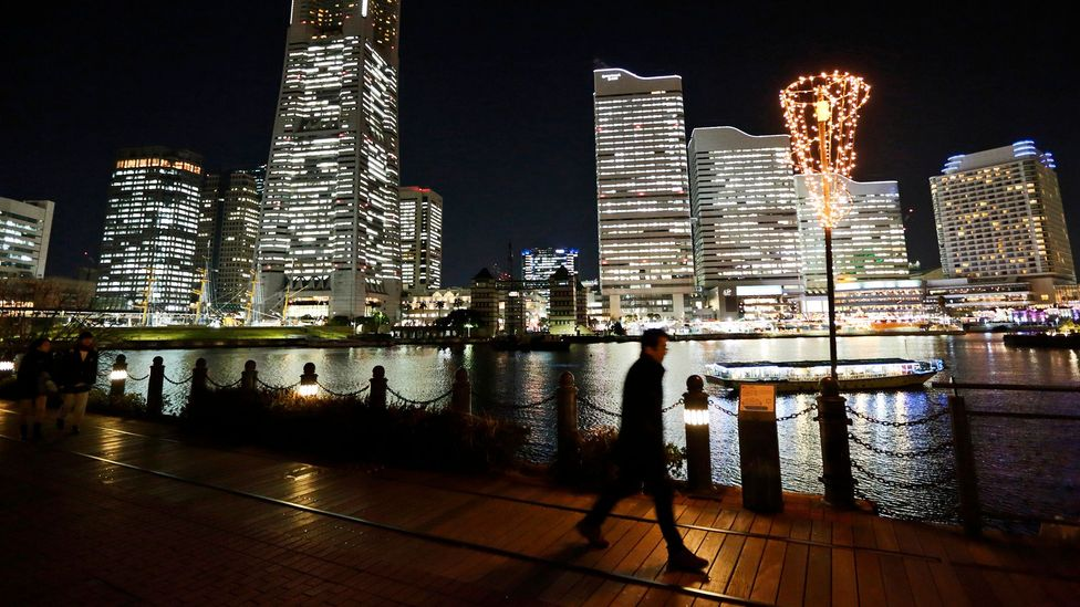 Despite the late hour and darkness, it's likely many are working inside these well-lit Tokyo buildings (Credit: Getty Images)