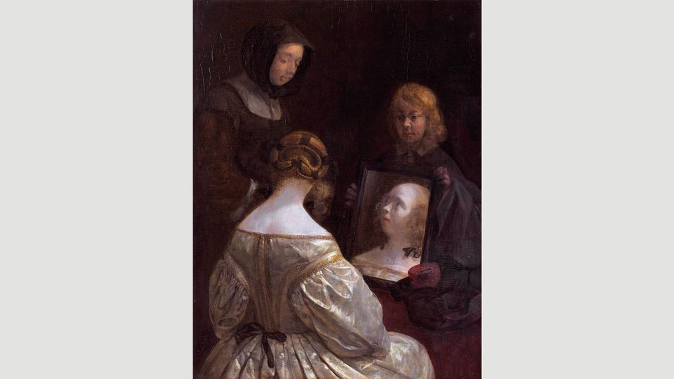 Gerard ter Borch's Woman at a Mirror shows a wealthy lady 'at her toilet', a recurring motif in 17th Century Dutch art (Credit: Rijksmuseum)
