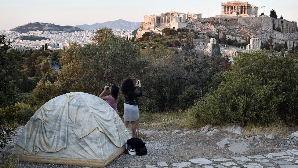 Rebecca Belmore'smarbletent, symbolising the refugee crisis in Greece, overlooks the Parthenon in Athens (Credit: Getty)