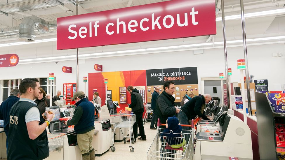 In many stores, four human cashiers could be replaced by one worker who directs crowds to banks of self-service tills - which many customers dislike (Credit: Alamy Stock Photo)