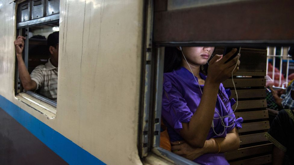 Woman using smartphone on train (Credit: Getty Images)