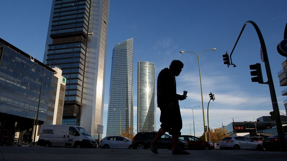 A man begs for food outside a financial district in Madrid (Credit: Getty Images)