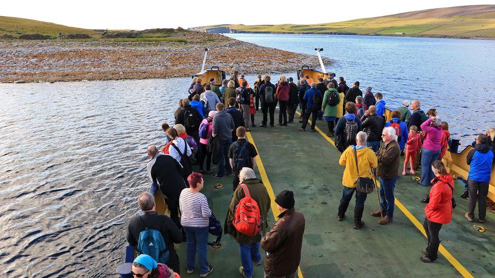 Passengers on the ferry wait as it pulls into Eynhallow (Credit: Mike MacEacheran)