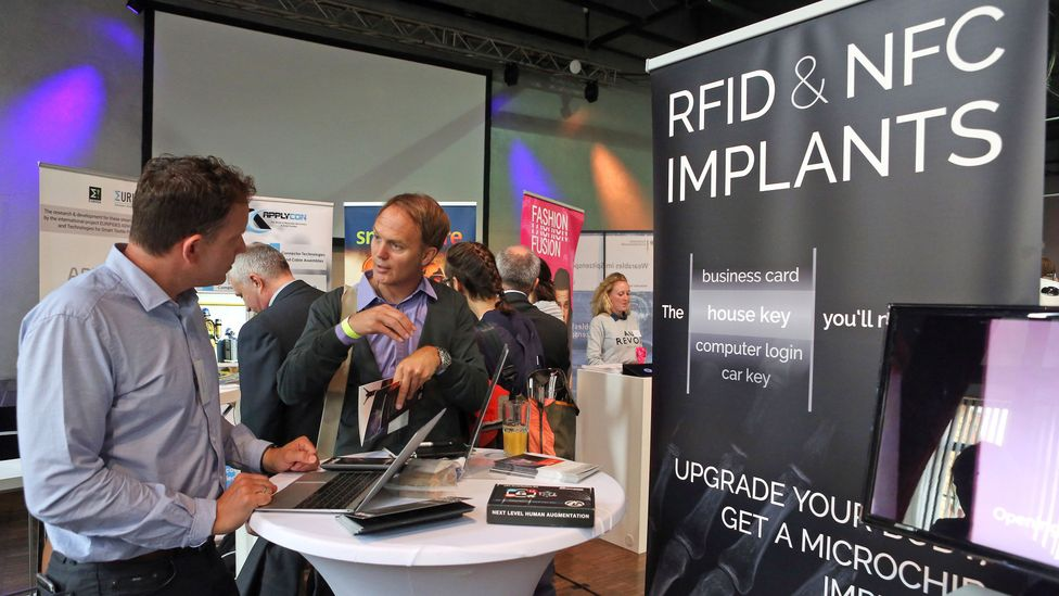 Visitors discuss microchip implants at the June 2017 Wear-it wearables festival in Berlin (Credit: Adam Berry/Getty Images)