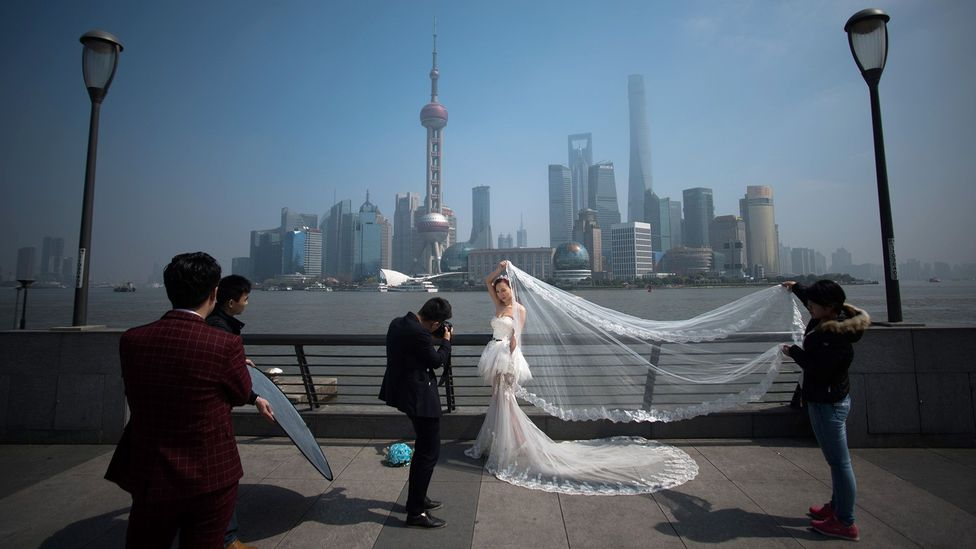 A woman poses for a wedding picture at the Bund in front of the financial district of Pudong in Shanghai (Credit: Getty Images)