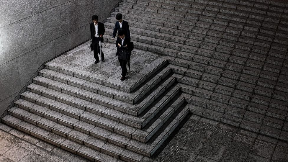 Young salarymen (office workers) leave an office building in Tokyo (Credit: Getty Images)