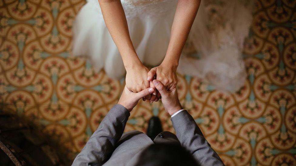 Newlyweds holding hands (Credit: iStock)