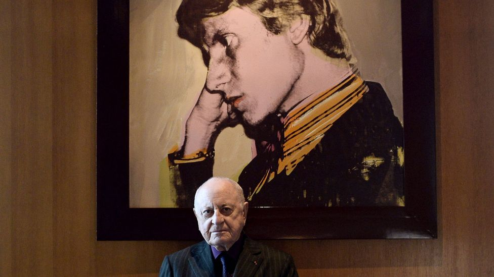 Saint Laurent's partner Pierre Bergé poses in front of an Andy Warhol portrait of the designer (Credit: Stephane de Sakutin/AFP/Getty Images)