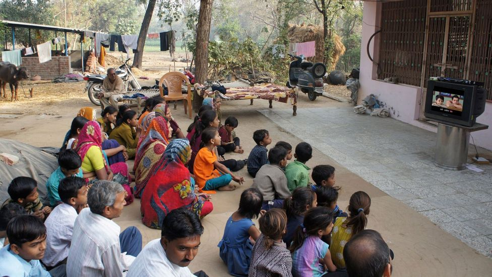 Villagers in Gujarat sitting together and following the lyrics of a Bollywood songs with subtitles. (Credit: PlanetRead)