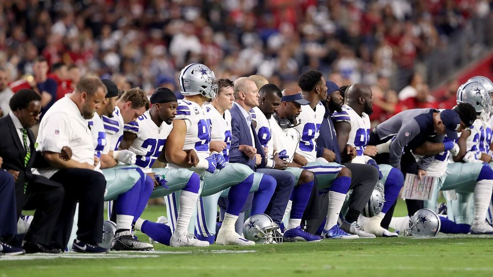 Members of the Dallas Cowboys kneel just before the US national anthem before the start of the NFL game against the Arizona Cardinals on 25 September 2017 (Credit: Getty Images)