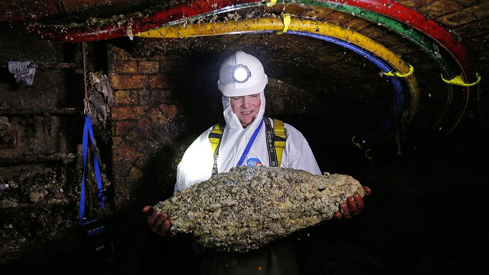A trunk sewer technician holds a 'fatberg' as he works in the intersection of the Regent Street and Victoria sewer in London (Credit: Adrian Dennis/AFP/Getty Images)