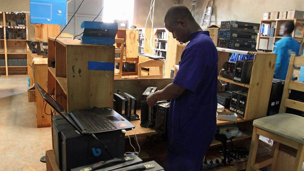 An electronic engineer fixes a broken BBOXX in the Kigali distribution center (Credit: Rachel Nuwer)