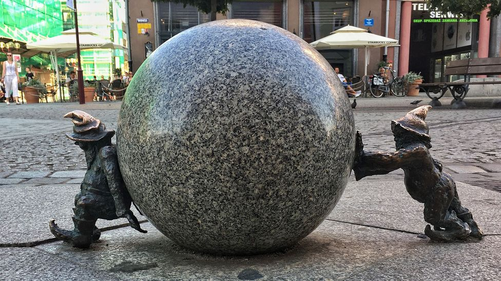 Wrocław's two most famous dwarves, nicknamed Sisyphus, push against each other (Credit: Eliot Stein)
