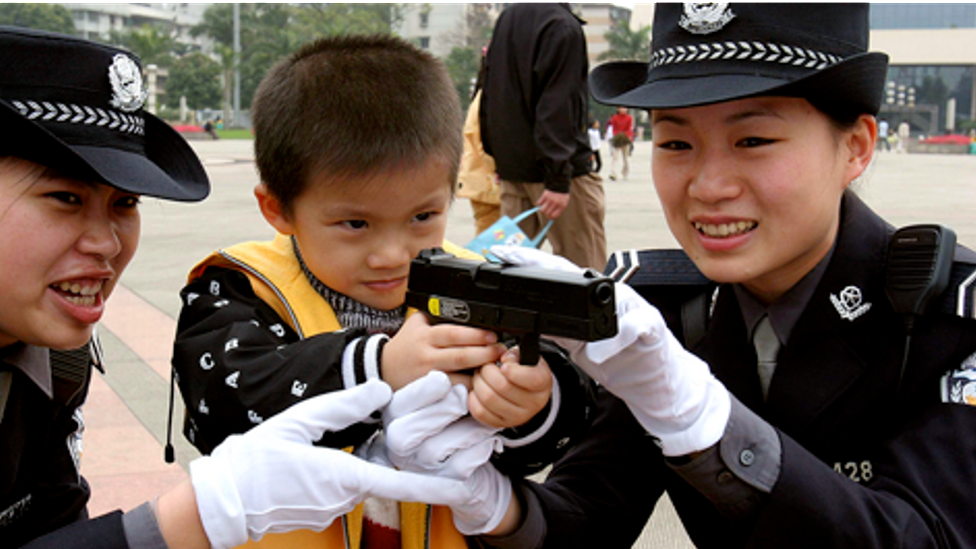 Members of the Policewoman Bicycle Patrol Team show a gun to a young boy in Nanning, China. (Credit: Getty Images)